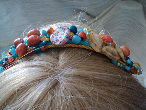 Serre-tête en feutrine bleu et ruban orange.Tout le haut du serre-tête est parsemé de perles orange et bleu de matières et tailles différentes,des perles en verre,céramique,porcelaine,bois,plastique et magiques