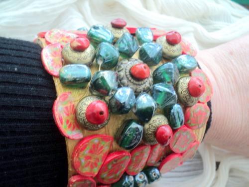 Bracelet sur feuille de bananier peinte,recouverte de ronds en p�te fimo et perles de verre vert et graines rouges
