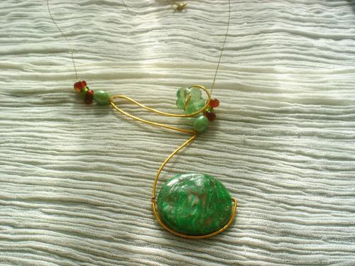 PIERRE DE LUNE: collier en  p�te fimo. Structure en fil d'aluminium dor� se terminant par un rond de p�te fimo vernie dans les tons vert.Le collier est aussi d�cor� avec d'un perle en verre verte en forme de fleur et petites perles rouges et vertes. Perles en porcelaine verte. Le tour de cou est un fil c�bl� dor� avec un fermoir mousqueton dor�