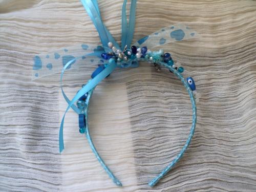 Serre-tête en tissus bleu et pois blancs décoré par un noeud blanc avec des coeurs bleus. Tout le serre-tête est recouvert de perles bleues et blanches en verre, bois, céramique, magiques....