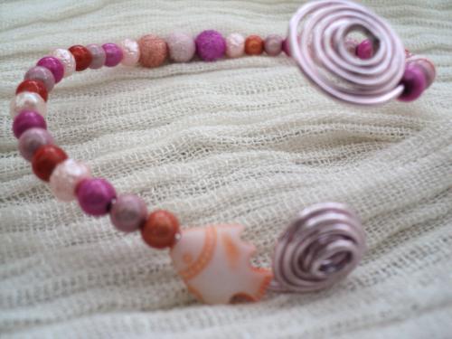 Bracelet sur fil d'aluminium sur lequel sont enfilées des perles en métal rose orange,violet et rose Au deux bouts le fil aluminium est entortillé et sur un bout un petit poisson orange et blanc Le bracelet grâce au fil d'aluminium peut se régler à toutes les tailles de poignet