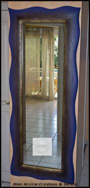 Miroir grand modèle en bois massif. Dim. : 180 x 68 cm. L'extérieur du cadre a reçu une magnifique couleur bleu lavande; l'intérieur, de la brou de noix avec un joli reflet doré délicatement appliqué à l'aérographe.