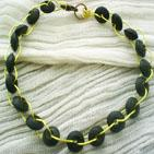 PETITE ROUE: Bracelet en fil d'aluminium jaune entrecrois� de perles en bois cylindrique aplaties: Fermoir � balance bronze.