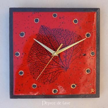 Horloge en lave émaillée Rouge nervure de feuille  Cette horloge Rouge nervure de feuille  en lave émaillée et touches d'or est une création unique. Dim : 25X25 cm Mécanisme silencieux. Fixation au dos