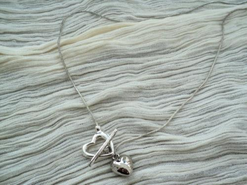 Collier fabriqué avec une chaîne en métal argenté et un coeur argenté qui passe au travers du fermoir.