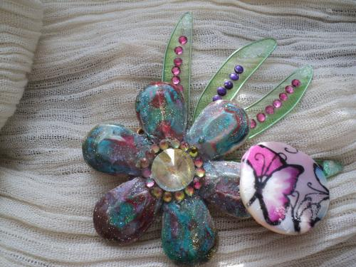 Broche en plastique peint avec des peintures prisma et moon et décorée d'un strass lumineux,sur le côté droit est collée une perle en porcelaine décorée d'un papillon peint
