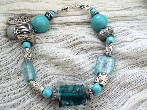 Bracelet,r�glable en perles bleues en verre, porcelaine et d�cor� de perles et breloques en m�tal argent�.