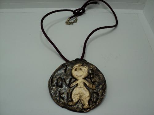 THE KID:Collier en p�te fimo, compos� d'un cercle de p�te fimo noir,une inscription