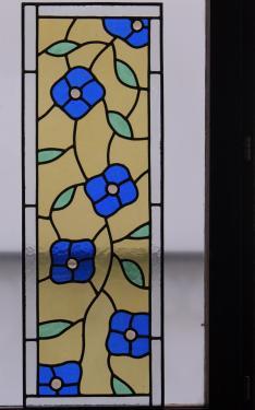 Vitrail motif floral pour fenêtre dans une montée d'escalier.