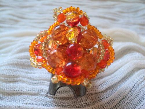 Bague sur anneau réglable en métal argenté composée de perles rondes en verre,orange et jaune,le pourtour est fait de perles rocailles orange.