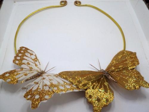 Torque en fil d'aluminium dor� sur le quel sont accroch�s deux papillons en plumes blanches et dor�es.