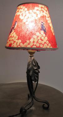 Abat-jour de forme conique habillé de tissu en lin avec des oiseaux bleus sur un fond rose indien. Une soutache en lin rehausse ce modèle qui est fixé sur un joli pied en fer forgé.