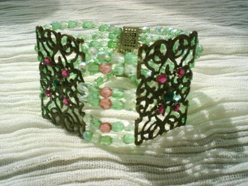 DIANA:Bracelet de six rangs de perles facettes de cristal swaroski, vert tendre et rose, orné de deux estampes bronze, ornées de petits strass roses et verts,3 fermoirs en métal décoré.  Superbe bracelet style ancien, qui sera du plus bel effet sur votre bras.