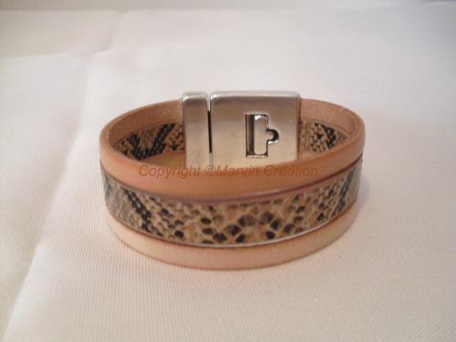Bracelet manchette (19 cm avec fermoir) 3 liens de cuir plat, 1 saumon, 1 imitation peau de serpent et 1 beige. Ce bracelet est fermé par un fermoir magnétique en métal argenté.  Il ne peut être mit à votre taille, c'est modèle unique. Réf: BRA04165