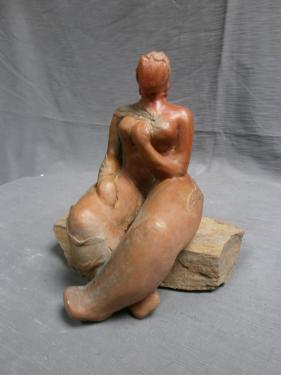 Petite femme assise socle pierre.
