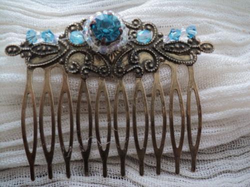 CAMILLE: Peigne à cheveux en bronze à décoration ancienne, sur laquelle a été rajouté au centre un strass bleu entouré d'un rang de rocailles blanches irisées. De chaque côté une perle facette en cristal de swaroski bleu et pour finir un rang de rocailles blanches irisées et de toupies en cristal de swaroski bleu.     Le peigne peut être doublé si vous désirez en mettre de chaque côté.Le deuxième sera à moitié prix