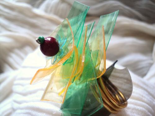 Bague réglable composée de chips en plastique vert et jaune empilées sur un clou doré. Le haut de la bague est composé d'une perle rouge et une rocaille verte