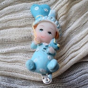 BAMBINO:Barrette à cheveux argentée, décorée d'un personnage en porcelaine peinte;