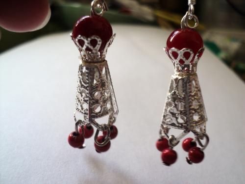 Boucles d'oreille composées d'un cône en métal argenté sculpté et de perles en plastique rouge.Le cône est surmonté d'une perles en porcelaine rouge et d'un crochet en métal argenté pour oreilles percées