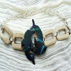 Grand bleu: Bracelet form� d'anneaux en m�tal argent� recouvert de cuir beige,au centre se trouvent deux dauphins en p�te fimo bleu d�grad�