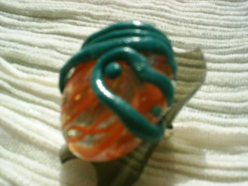 SPIRALE:Bague sur anneau réglable argenté,surmonté d'un galet transparent et orange, entouré d'un fil vert en pâte fimo. Largeur du galet: 3cm