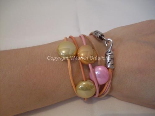 Bracelet (35 cm avec fermoir) 4 liens de cuir fin rond de couleur rose, orange, beige et saumon. Des perles palet dans les mêmes tons agrémentes les liens de cuir. Un fermoir crochet en métal vieil argent termine le bracelet. Ce dernier se porte en double. Il ne peut être mit à votre taille, c'est un modèle unique. Réf: BRA04161