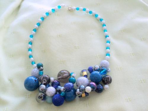 Collier ras du cou en perles ronds en verre blanc et gris.Les autres sont en perles de toutes tailles,de toutes matières verre, porcelaine,cristal...de couleurs bleus et grises