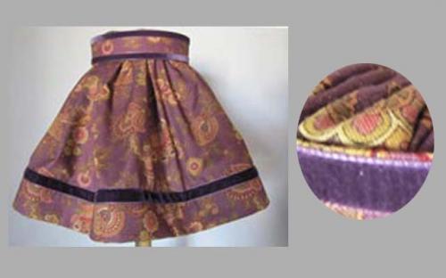 Abat-jour juponné réalisé dans un tissu style Perse Ancienne dans les tons de mauve,le tout souligné par un galon de velours haut et bas en rappel de la jupe.