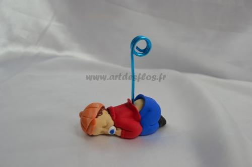 Bébé Titi Parisien Produit fait main. Bébé en pâte polymère (fimo). Pantalon bleu, pull rouge et sa casquette marron. L 3 cm / l 6.5 cm / H 3 cm Pays d'expédition : France. + 3,00 de frais de port