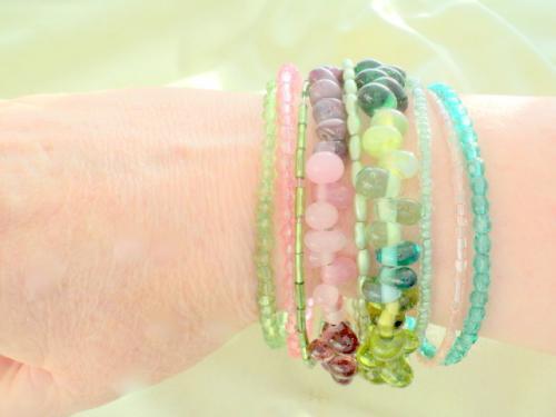 Bracelet m�moire 9 rangs compos� de perles de verre rose et vert,de toutes tailles et formes,rocailles,facettes,toupies. Les rangs sont reli�s par un clou d�cor� de de rocailles vertes.fermeture par crochets