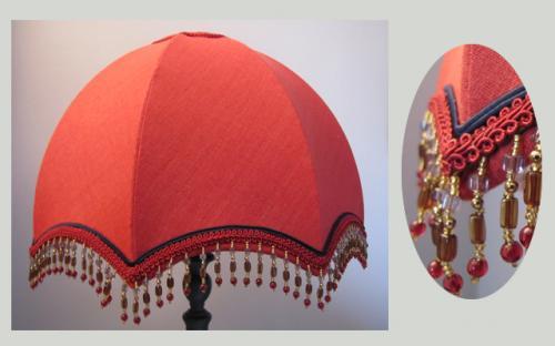 Confectionné dans un lin  rouge oriental, cet abat-jour dôme est doublé d'un voile de coton au ton  bleu marine. Il est agrémenté de soutache, galon épi de blé et de perles reprenant les couleurs de la jupe et de son intérieur.