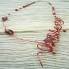 CHI-CHI: Collier en fil d'aluminium rose, en forme de cage sur un côté, l'autre côté présente une enfilade de perles de verre violine,de facettes roses claires de perles de nacre rose,de perles en fer rose et rocailles violines. La cage contient des fil de cuivre sur lesquels pendent les mêmes perles.