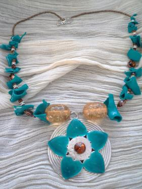 Collier mi-long composé d'un pendentif en métal argenté, décoré de pétales turquoise et une perle ambre.Deux grosses perles en verre démarre le pourtour composé de chips en plastique turquoise,de perles rondes ambre et des perles en métal argenté. Fermoir balance