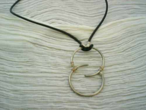 HUIT: Collier composé de deux demi-cercles et d'un lien en cuir avec un fermoir mousqueton argenté.