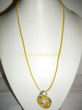 Collier (55 cm avec fermoir sans médaillon), cuir rond jaune, fin et médaillon rond de 3 cm jaune en métal argenté avec petites fleurs.le fermoir est un mousqueton en métal argenté. Ce collier peut être ajusté.  Me contacter pour renseignements Réf: CO04163