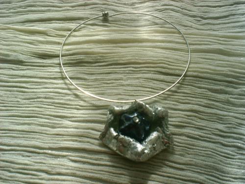 VENISE: Pendentif sur torque en métal argenté, pendentif en pâte fimo grise craquelée vernie.En son centre un galet bleu au coeur décoré d'un strass