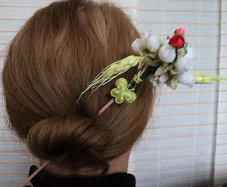 MAI:Pic à cheveux: sur une tige en bois peint en rose et verni, est accroché à son extrémité un bouquet de fleurs blanches en tissu et de roses rouges.Des épis de blés verts complètent ce bouquet champêtre. Un peu plus bas sur la tige est posé un petit papillon en satin vert.