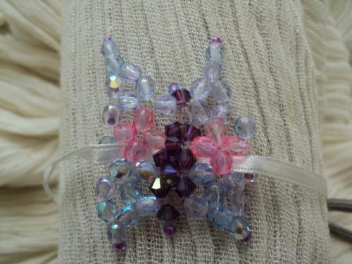 PAPILLON: bracelet en perles enfant  Bracelet en perles sur ruban en soie grise, r�glable pour toutes les tailles de poignet. Le papillon est compos� de facettes violine iris� pour les ailes ainsi que de la rocaille rose. Le corps du papillon est fabriqu� avec de toupies violette. Bracelet aux couleurs du printemps
