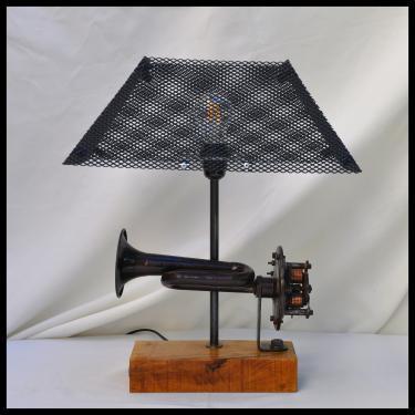 Lampe Klaxon 1930 Un klaxon 6 volts des années 30 environ, un pied en chêne et un abat-jour réalisé avec une grille en acier peint en noir et équipé d'une ampoule leds à filaments de 4 watts.