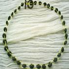 GRANDE ROUE: Collier en fil d'aluminium jaune entrecroisé de perles en bois cylindrique aplaties. Fermoir anneau en bronze Parure collier+bracelet+bague: 20,00 euros