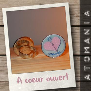 Bague « A c?ur ouvert » - ATOMANIA  composée d?une image créée par « Atomania », protégée par résine transparente, montage sur support de bague argenté réglable. Format : 25 mm.