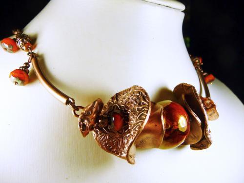 Collier court type tour de cou souple compos� de disques ondul�s en cuivre textur� et patin� enserrant une perle en c�ramique grecque orange marbr�e et iris�e. Le motif central est reli� par des �l�ments en m�tal cuivr�, des perles de verre tch�ques � facettes oranges opalescentes � finition marbr�e, des perles de cuivre, et termin� par une cha�ne. Fermeture � mousqueton et cha�nette de rallonge.  Pi�ce unique de cr�ation artisanale en cuivre fusionn�.  Verni de protection.  Longueur totale : 53,5 cm (soit 60 cm avec la cha�nette de rallonge).  Motif central : Largeur 8 cm - Hauteur 3,5 cm - Profondeur 2 cm  Poids : 62 gr. Mat�riaux utilis�s : C�ramique Cuivre