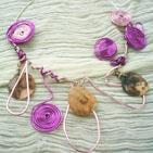 DUO ROSE:Torque argenté sur laquelle s'enroule un fil d'aluminium rose et un violet, ces deux fils sont de ci de là enroulés en cylindre.Sur le devant du collier on trouve des perles de nacre beige  et des facettes roses ainsi que des vagues formées par le fil d'aluminium