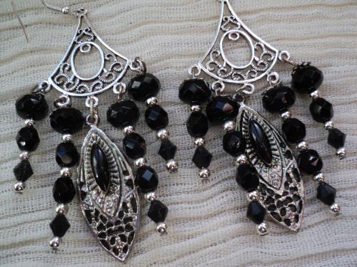 Boucles d'oreille pour oreilles percées composées d'une estampe en métal argenté sur laquelle pendent quatre branches de perles de perles noires, des toupies,des facettes et des facettes aplaties ces perles sont séparées entre-elles par des perles rondes en métal argenté.Au centre une estampe décorée d'un perle noire