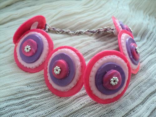 Bracelet composé de  rondelles en pâte fimo fabriquées de plusieurs étages de pâte fimo rose et mauve et se termine par une perle en métal argenté. Les rondelles sont reliées par deux fils de coton rose et mauve.