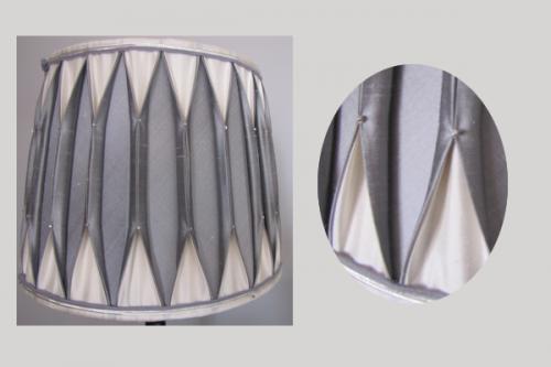 Abat-jour conique  confectionné  dans les  deux tons gris et ivoire en soie plissée à la main et smoké à l'aide de fines perles argentées. Une double soutache gris et argent souligne le haut et bas et complète avec raffinement l'ensemble.