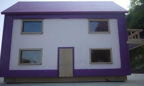 Maison de poupée en bois comprenant :  une cuisine équipée de 20 sur 26.5 cm,  un salon de 26.5 sur 28.5 cm,  une salle de bain de 20 par 26.5 cm équipée d'un meuble vasque une douche et une baignoire,  une petite chambre de 20 par 26.5 cm  une grande chambre de 26.5 par 50 cm.    Chaque pièce possède une fenêtre à double vantaux en plexi de 8mm, sauf la petite chambre qui présente une fenêtre coulissante donnant sur le balcon. Une fenêtre dans le salon et une porte dans la cuisine sont situées sur la face arrière de la maison.  Les murs sont tapissés avec du papier peint qualité française et les sols sont en vinyle. La peinture utilisée présente l'EU Ecolabel: fr/07/015 et lessivable avec des produits ménagers courants.