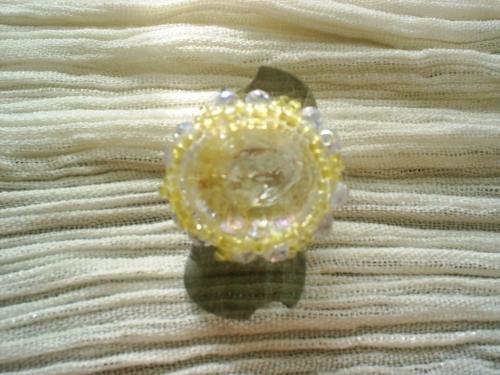 BERLINGOT  bague sur plateau, anneau argent� r�glable surmont� d'un cabochon iris� entour� de facettes de cristal de swaroski bleu clair et perles de rocaille jaune.     Taille de la bague 2 cm.