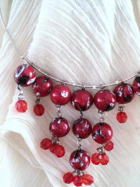 Collier sur trois rangs de perles en céramique rouge décorées de motifs blancs. De ces perles pendent des perles en plastique rouge
