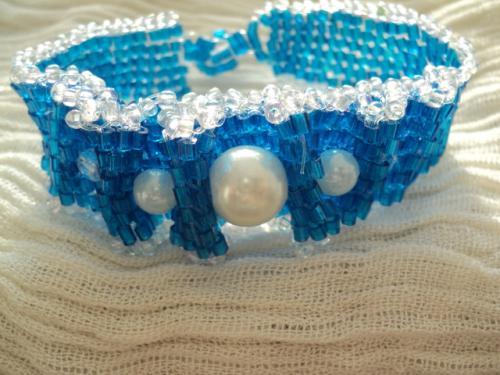 Bracelet en perles de rocailles et perles de culture. Les rocailles sont tissées et le dessus est plié en plusieurs vagues et retiennent les perles de culture. Fermoir perles
